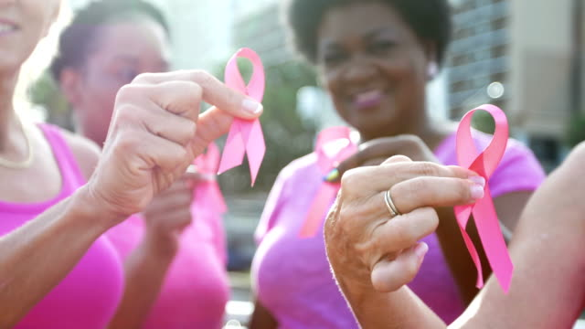 vídeos de stock e filmes b-roll de women holding breast cancer awareness ribbons - cancro