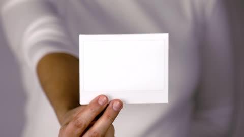 vídeos y material grabado en eventos de stock de las mujeres sosteniendo marco de fotos instantánea - transferencia de impresión instantánea