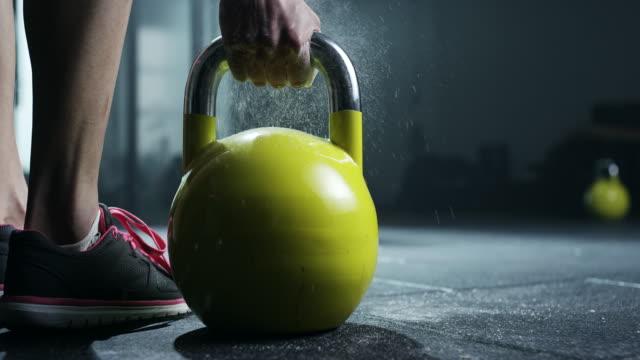 vídeos de stock, filmes e b-roll de mulheres segurando o kettlebell no ginásio - peso livre equipamento para exercícios