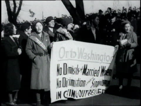 women holding up a banner demanding equal rights for married women in receiving welfare relief / policeman monitoring the crowd - 1932 stock-videos und b-roll-filmmaterial