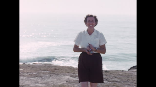 stockvideo's en b-roll-footage met a women holds a 16 mm video camera and shoots the filmmaker on a beach. - 1940