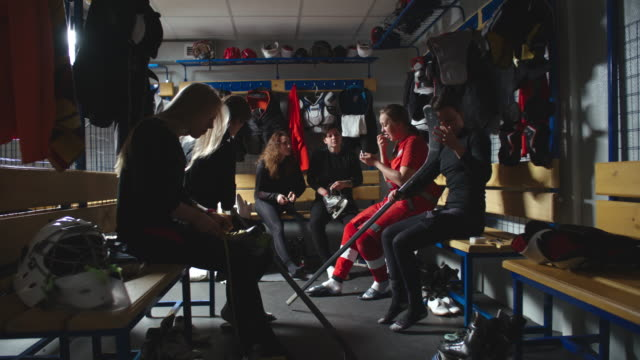 Women ice hockey team talking and getting ready for practice