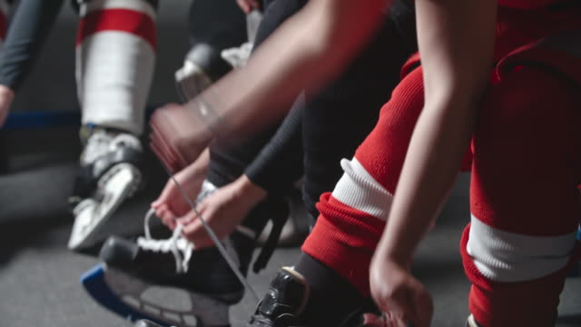 women ice hockey team tying skates before practice - locker room stock videos and b-roll footage