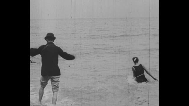 women in 1910 at brighton beach in england in bathing costumes play on beach and in water / man in bowler hat, jacket and rolled up pants wades at... - swimwear stock videos & royalty-free footage
