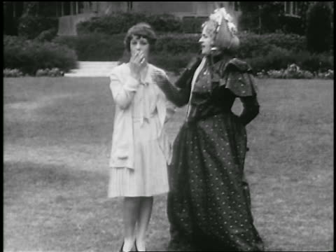 b/w 1929 women in 19th c. dress removing cigarette from flapper's lips / pasadena / newsreel - 1920 1929 stock videos & royalty-free footage