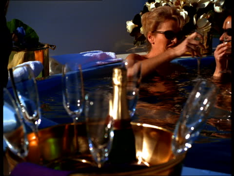 Women in a hot tub toast and drink Champagne.