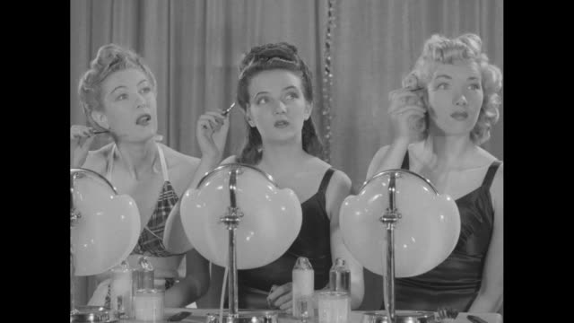 vidéos et rushes de women in bathing suits lying on their backs in two rows apply face cream to their faces / three women sitting at makeup tables listening to... - mascara