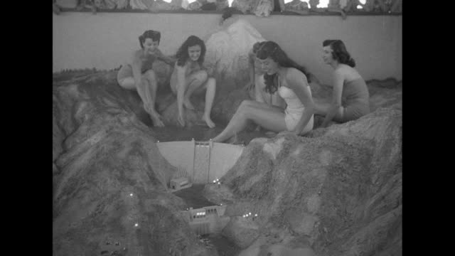 women in bathing suits sit with legs in part of a working diorama of a dam in the central valley project, which will control water flow in... - other stock videos & royalty-free footage