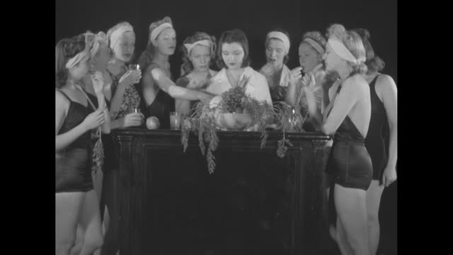 vídeos de stock, filmes e b-roll de women in bathing suits standing around counter eating vegetables and fruit / cu nurse applying wax beauty bath / cu woman eating grapes / note exact... - estudante universitária