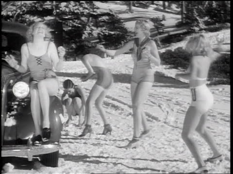vídeos de stock e filmes b-roll de b/w 1936 women in bathing suits throwing snowballs at each other near car - fato de banho
