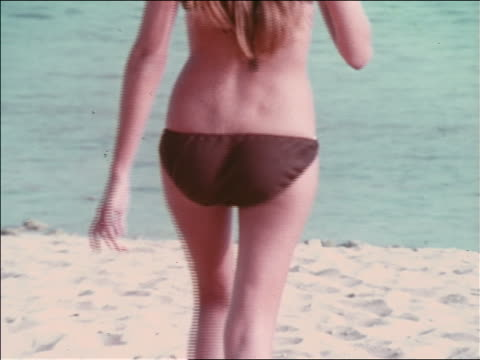 1969 montage women in bikinis on beach - walking, sunbathing, talking, legs, cleavage, buttocks - bikini stock-videos und b-roll-filmmaterial