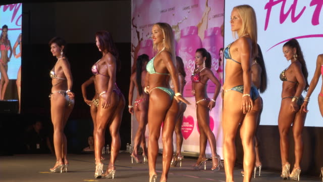Women in bikinis pose on stage during the Fit Angel Classic Bodybuilding competition in Bangkok Thailand
