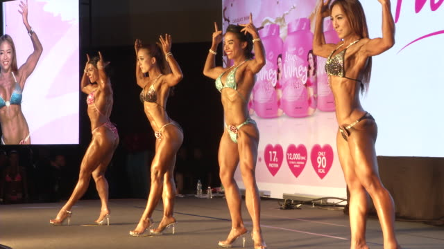 women in bikinis pose on stage during the fit angel classic bodybuilding competition in bangkok thailand - body building bildbanksvideor och videomaterial från bakom kulisserna