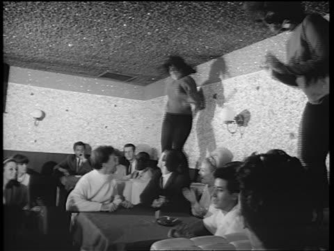 B/W 1965 2 women in black tights dancing on table in nightclub as crowd claps / newsreel