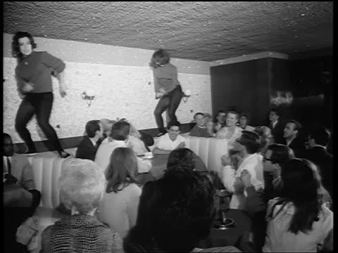 b/w 1965 2 women in black tights dancing on table in nightclub as crowd claps / newsreel - tights stock videos & royalty-free footage