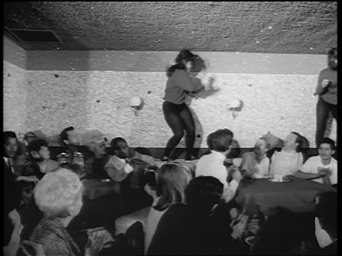 B/W 1965 PAN 2 women in black tights dancing on tables in nightclub as crowd claps / newsreel