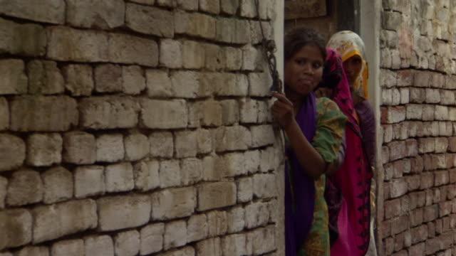 MS Women in brightly colored saris looking out of doorway, Agra, Uttar Pradesh, India