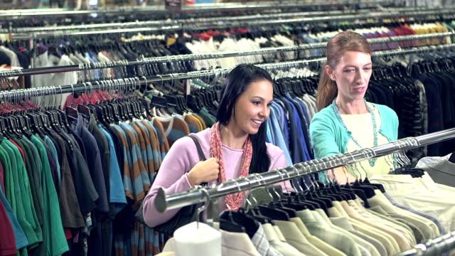 Women in clothing store shopping for men's shirts