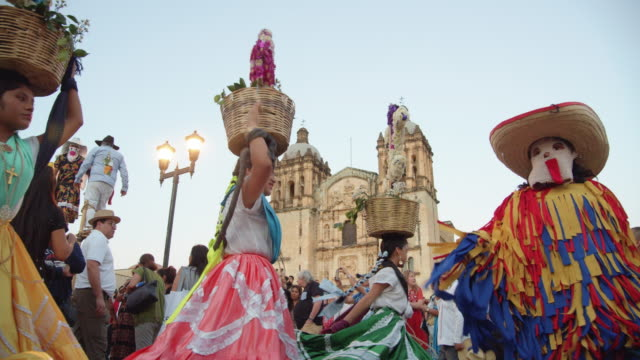 women in colorful attires parading baskets of flowers in front of oaxaca cathedral during a traditional calenda parade in oaxaca, mexico - puppet stock videos & royalty-free footage