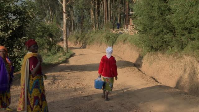 Women in colorful dress walk down dirt road in Rwanda.