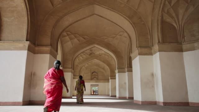 ls women in colorful saris walking a corridor on the grounds of sikandra/ agra, uttar pradesh, india - 史跡めぐり点の映像素材/bロール