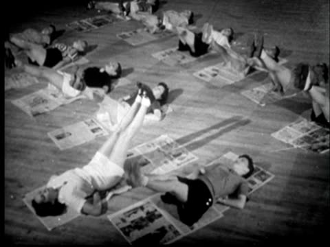 1945 film montage ha ws women in exercise class lying on their backs and lifting their legs/ ms woman with legs up/ ms little girl pulling her mother's legs down/ sylacauga, alabama - home workout stock videos & royalty-free footage