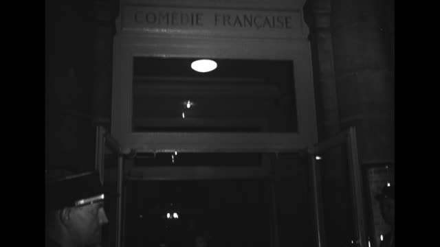 MS women in formal wear entering the Comedie Francaise / Pan up to sign over entrance / With a crowd of people around Oona O'Neill in white fur...