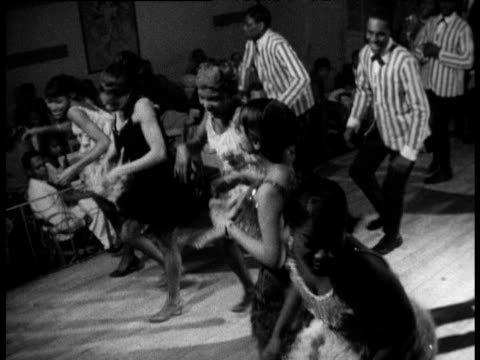 Women in fringed dresses and men in striped jackets dance 'Hully Gully' in Harlem nightclub New York 1960's