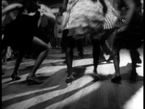 Women in fringed dresses and men in striped jackets dancing 'Hully Gully' in Harlem nightclub New York 1960's