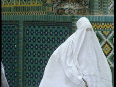 stockvideo's en b-roll-footage met women in full burkha walk through grounds of blue mosque tomb\nof hazrat ali mazar i sharif; 1975 - afghanistan