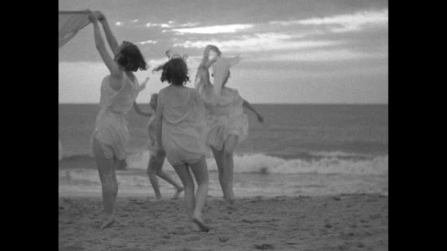 vídeos de stock, filmes e b-roll de women in grecian costumes dance while holding sheer scarves with the ocean and sunrise beyond - véu