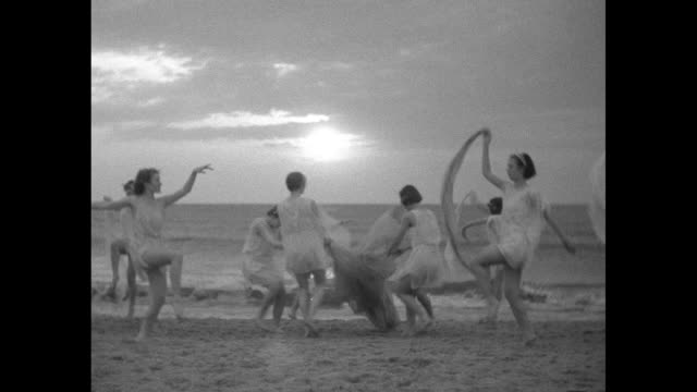 vídeos de stock, filmes e b-roll de women in grecian costumes dancing in a loosely choreographed circular dance with ocean and sunrise beyond - véu