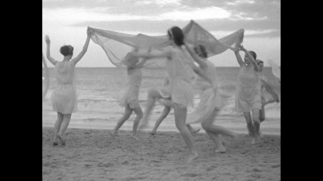 vídeos de stock, filmes e b-roll de women in grecian costumes dancing under and around a square sheer diaphanous cloth with ocean and sunrise beyond - véu