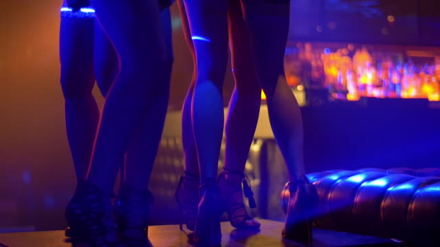 TU SLO MO Women in high heels dancing on nightclub table