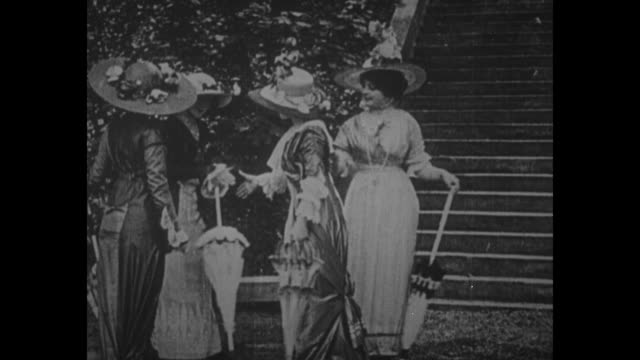 women in large hats and formal dresses, each with a purse or a parasol, mingle outdoors, next to steps of a building, probably at a garden party in... - party hat video stock e b–roll
