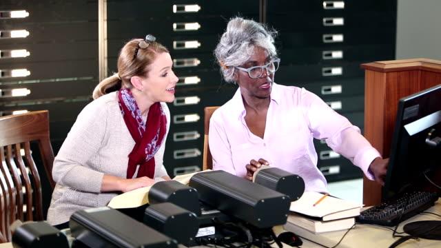 vídeos de stock, filmes e b-roll de mulheres na biblioteca que fazem a pesquisa com leitor do microfilme - 40 49 anos