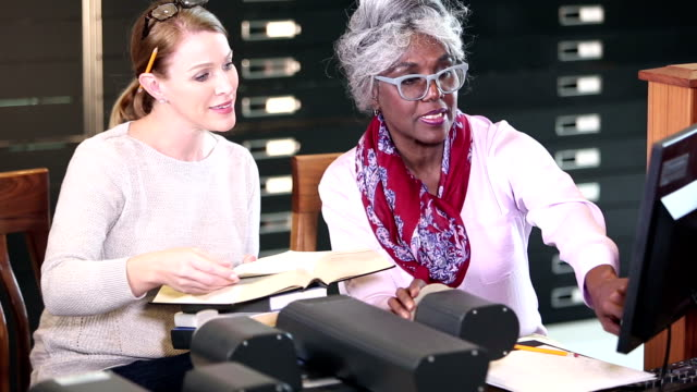 women in library doing research with microfilm reader - librarian stock videos & royalty-free footage