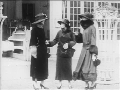 stockvideo's en b-roll-footage met b/w 1917 3 women in long coats + hats shaking hands + talking on sidewalk - 1917