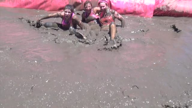 women in obstacle race go down slide into mud pit - salmini 個影片檔及 b 捲影像