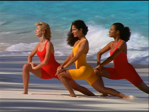 3 women (1 Black, 1 Hispanic) in orange + yellow leotards stretching in unison on beach / Bahamas