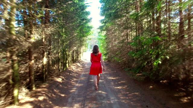 Women in red dress walking in the tree alley