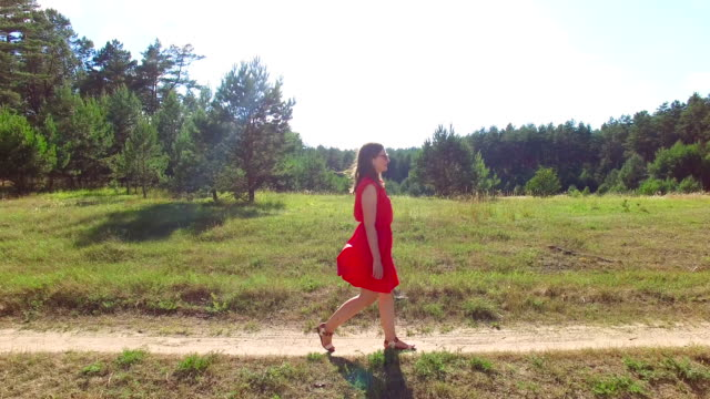 Women in red dress walking on the road