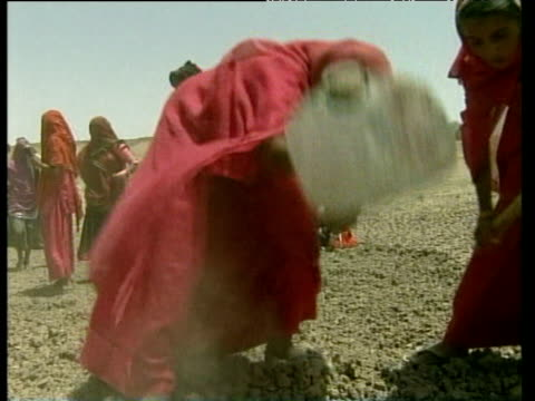 Women in red saris dig in dry soil during drought 02 May 00