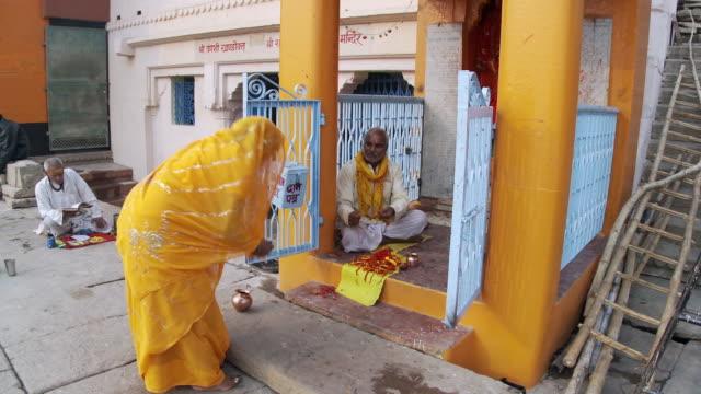 women in sari worshipping at temple - dhoti video stock e b–roll