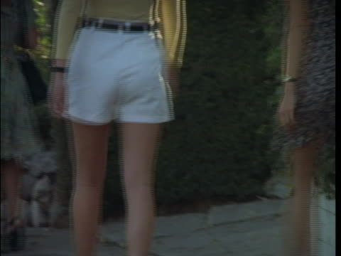 women in shorts and dresses walk along a crowded sidewalk. - shorts stock-videos und b-roll-filmmaterial