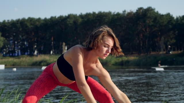 frauen im sport. schöne mädchen beim yoga am see - 20 29 years stock-videos und b-roll-filmmaterial
