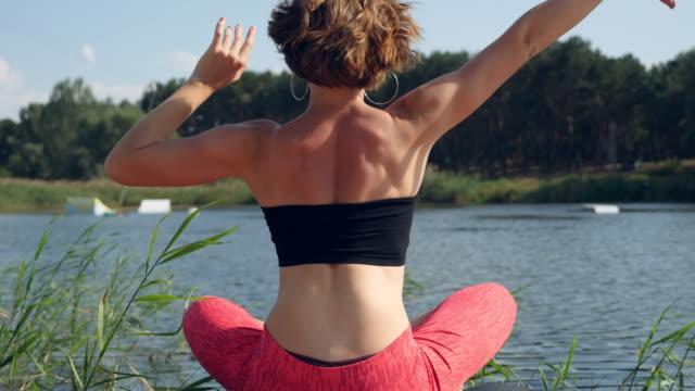 vídeos de stock, filmes e b-roll de mulheres no esporte. linda garota fazendo yoga no lago - 20 29 years