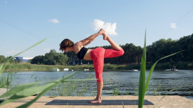Women in Sport. Beautiful girl doing yoga at the lake