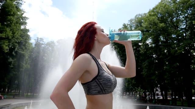 Frauen im Sport. Schöne Mädchen Sportler trinkt Wasser. Slow-motion