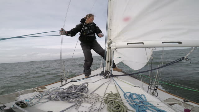 women in sport: female solo sailor dropping the jib - matrose stock-videos und b-roll-filmmaterial